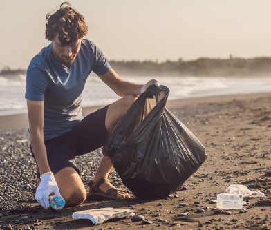 man cleaning up garbage on the beach